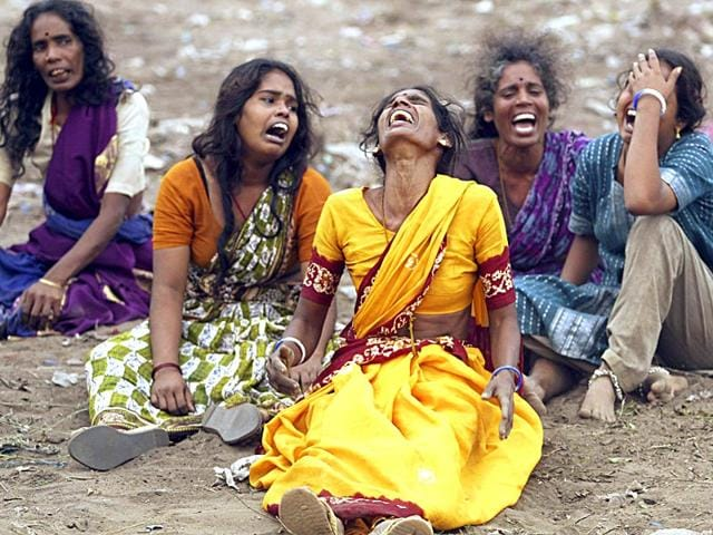 Indian women mourn the death of their families killed in the tsunami in Madras, in December 2004. (Reuters)