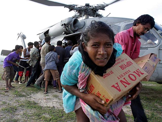 Tsunami refugees receive supplies distributed by the USS Abraham Lincoln Carrier Strike Group in Krueng Raya, northeast of Banda Aceh, Indonesia in January 2005. (Reuters)