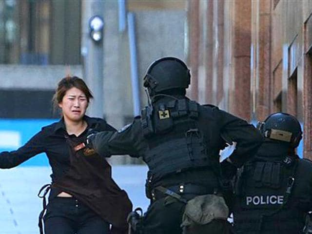 A hostage runs to armed tactical response police officers for safety after she escaped from a cafe under siege at Martin Place in the central business district of Sydney, Australia. (AP Photo/Rob Griffith)
