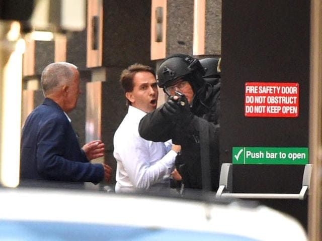 Armed police evacuate employees from the offices next to a cafe in the central business district of Sydney. (AFP photo)