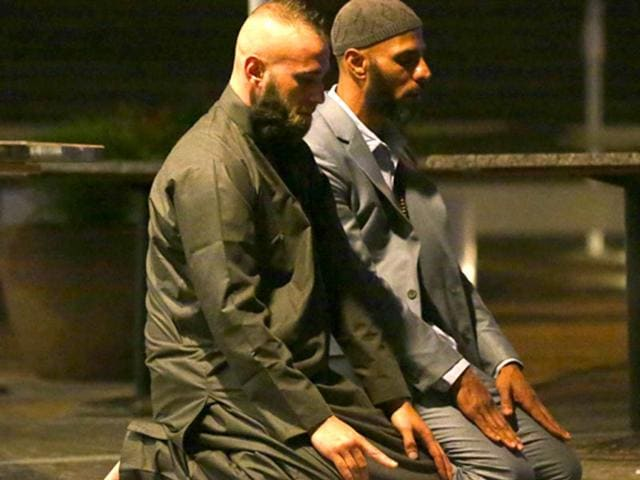 Sam Tiger right, and Abdulrahman El-Lawn perform prayers after a cafe siege in Sydney. This was their first prayer of the morning and prayed for peace and to bring comfort upon those affected especially the hostages and their families. They both made a second prayer directed towards Muslims to make the aftermath a peaceful one. AP Photo