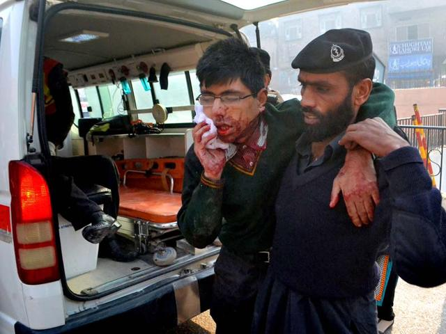 A-student-injured-in-the-shootout-at-Army-Public-School-in-Pakistan-s-Peshawar-is-helped-by-a-hospital-security-guard-AP-Photo