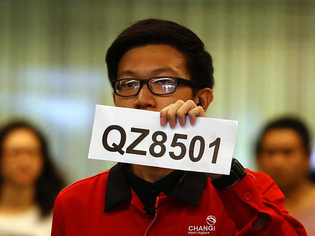 A-Changi-Airport-staffer-holds-up-a-sign-to-direct-possible-next-of-kins-of-passengers-of-AirAsia-flight-QZ-8501-from-Indonesian-city-of-Surabaya-to-Singapore-at-Changi-Airport-in-Singapore-Reuters