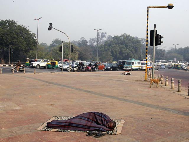 Life-in-the-metro-goes-on-unaware-of-the-condition-the-homeless-face-in-the-capital-A-man-catches-up-on-his-sleep-on-a-pavement-near-Nizamuddin-in-south-Delhi-as-life-goes-on-in-the-city-Subrata-Biswas-HT-Photo