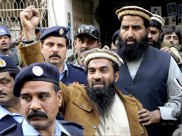 Zaki-ur-Rahman-Lakhvi-the-main-suspect-of-the-Mumbai-terror-attacks-in-2008-raises-his-fist-after-his-court-appearance-in-Islamabad-Pakistan-AP-File-Photo