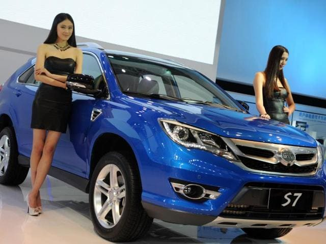 A-model-poses-next-to-a-BYD-S7-SUV-on-media-day-at-the-Shanghai-auto-show-in-Shanghai-on-April-20-2013-Photo-AFP