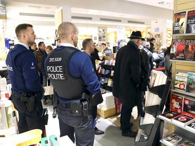 Belgian-police-officers-stand-guard-in-a-bookstore-as-people-queue-to-buy-the-first-edition-of-Charlie-Hebdo-published-after-the-deadly-attacks-by-Islamist-gunmen-in-Paris-last-week-in-Brussels-Reuters