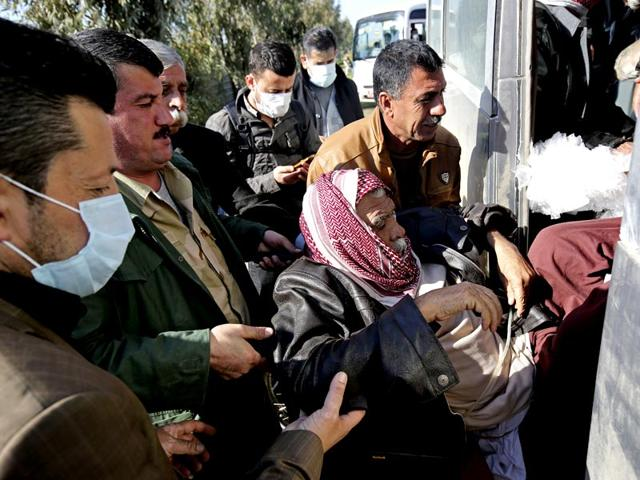 An-elderly-disabled-Yazidi-man-is-carried-to-a-bus-that-will-bring-him-to-the-Kurdish-city-of-Dohuk-after-being-released-by-Islamic-militants-in-Alton-Kupri-outside-Kirkuk-Iraq-AP-Photo