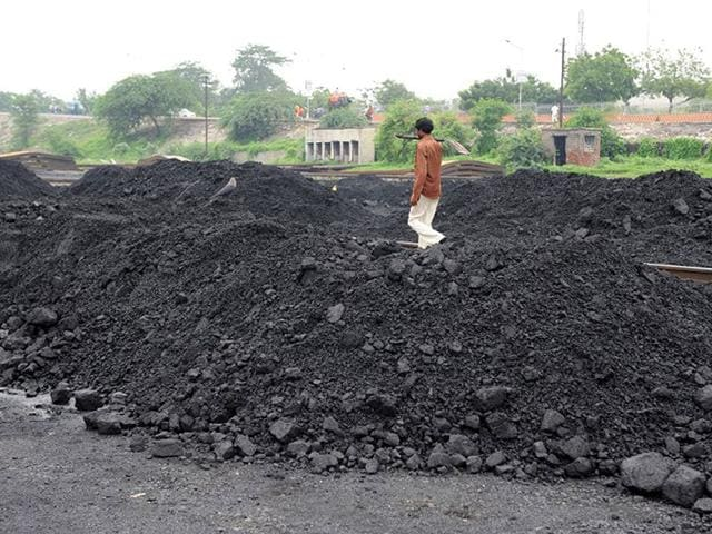 A-labourer-walks-past-mounds-of-coal-at-the-Kankaria-Railway-yard-in-Ahmedabad-AFP-file-photo