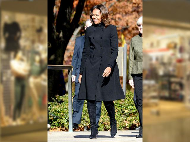 During a ceremony to honor veterans at the Tomb of the Unknowns, Michelle Obama breaks out a double breasted black Burberry coat that