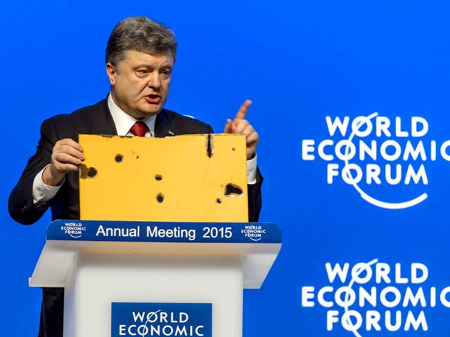 Ukrainian-President-Petro-Poroshenko-holding-a-part-of-a-commuter-bus-that-was-hit-by-a-rocket-that-killed-13-people-He-was-speaking-at-the-World-Economic-Forum-in-Davos-Switzerland-AFP-Photo