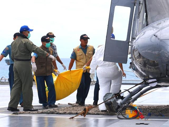 Military-personnel-load-a-bodybag-containing-what-they-believe-to-be-a-victim-of-AirAsia-QZ-8501-onto-a-helicopter-on-the-deck-of-Indonesian-Navy-ship-sailing-in-the-Java-Sea-Indonesia-AP-Photo