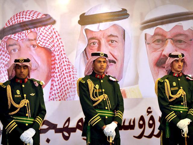 Saudi-royal-guards-stand-on-duty-in-front-of-portraits-of-King-Abdullah-bin-Abdulaziz-R-Crown-Prince-Salman-bin-Abdulaziz-C-and-second-deputy-Prime-Minister-Muqrin-bin-Abdulaziz