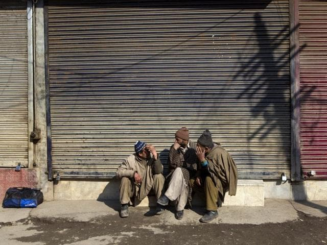 Kashmiri--labourers-chatting-as-they-sit-outside-a-closed-market-during-a--shutdown-AP-Photo