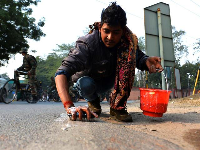 A worker scrubs the road to the Taj Mahal in Agra ahead of US President Barack Obama