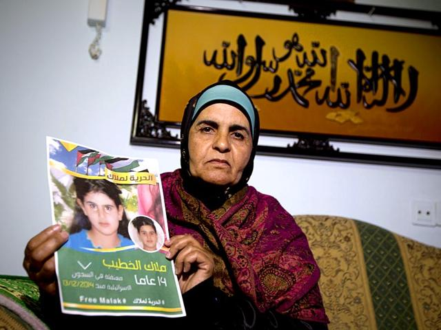 Khawla-Al-Khatib-holds-a-poster-of-her-14-year-old-daughter-in-Beitin-near-Ramallah-AP-Photo