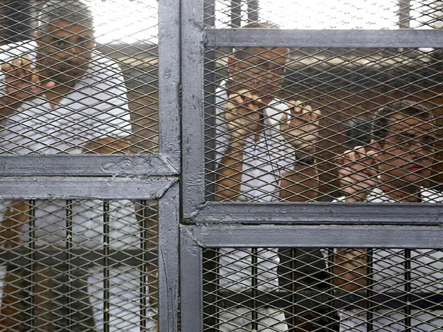 Al-Jazeera-journalists-L-R-Peter-Greste-Mohammed-Fahmy-and-Baher-Mohamed-stand-behind-bars-at-a-court-in-Cairo-in-this-June-1-2014-file-photograph-Reuters-Photo