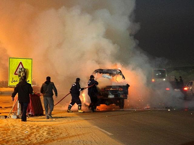Egyptian-firefighters-extinguish-fire-from-a-vehicle-outside-a-sports-stadium-in-a-Cairo-s-northeast-district-during-clashes-between-supporters-of-Zamalek-football-club-and-security-forces-AP-Photo
