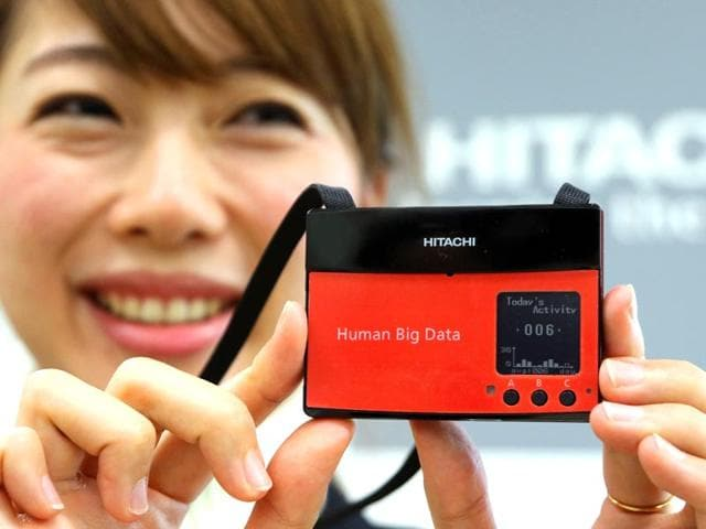 Japan-s-electronics-giant-Hitachi-employee-displays-the-new-wearable-sensor-which-measures-human-activity-of-the-group-or-organization-and-analyze-happiness-tendency-of-the-group-to-boost-productivity-at-the-company-s-headquarters-in-Tokyo-AFP-photo
