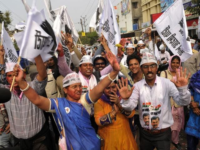 AAP-volunteers-wield-brooms-the-party-s-poll-symbol-as-they-celebrate-outside-the-Patel-Nagar-party-office-Arvind-Yadav-HT-Photo