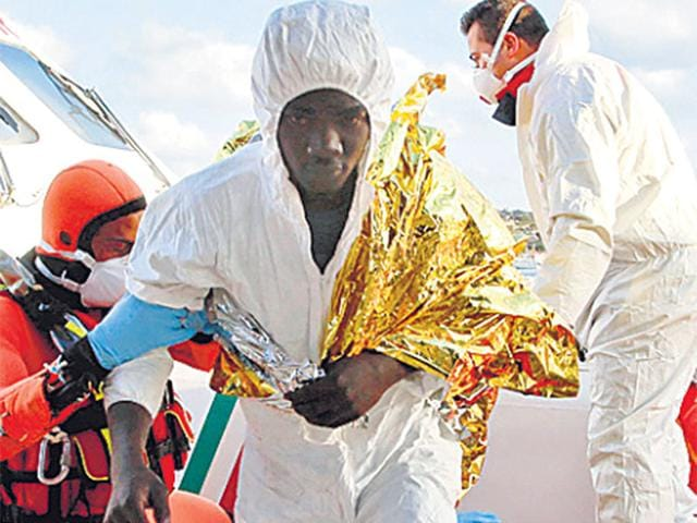 A-migrant-who-survived-a-shipwreck-is-helped-on-to-Lampedusa-harbour-in-Italy-on-Wednesday-Reuters