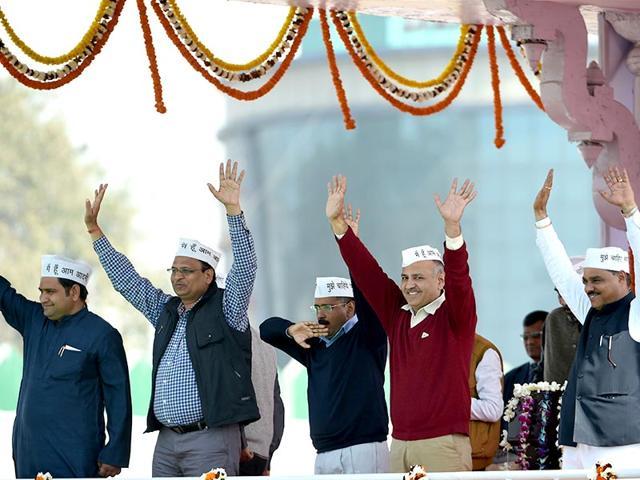 Delhi CM Arvind Kejriwal (C) and fellow AAP ministers Sandeep Kumar, (L), Asim Ahmed Khan (2L), Satyendra Jain (3L), Gopal Rai, (3R), Manish Sisodia (2R) and Jitender Singh Tomar (R) greet supporters during the swearing-in ceremony at Ramlila Maidan. (AFP PHOTO)