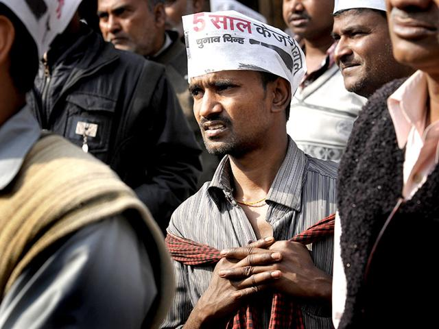 AAP supporters look at the screens installed near Ramlila Maidan for Kejriwal's swearing-in ceremony. (HT photo/Saumya Khandelwal)