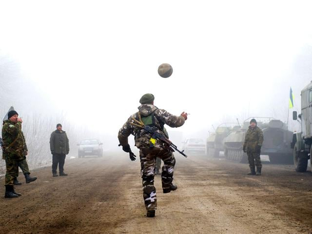 Ukrainian-servicemen-play-football-on-a-road-at-Svitlodarsk-approaching-Debaltseve-A-ceasefire-in-Ukraine-was-cautiously-observed-by-both-sides-despite-accusations-by-Kiev-and-the-US-that-Russia-had-fuelled-a-final-push-by-rebels-to-gain-territory-before-the-deadline-AFP-photo