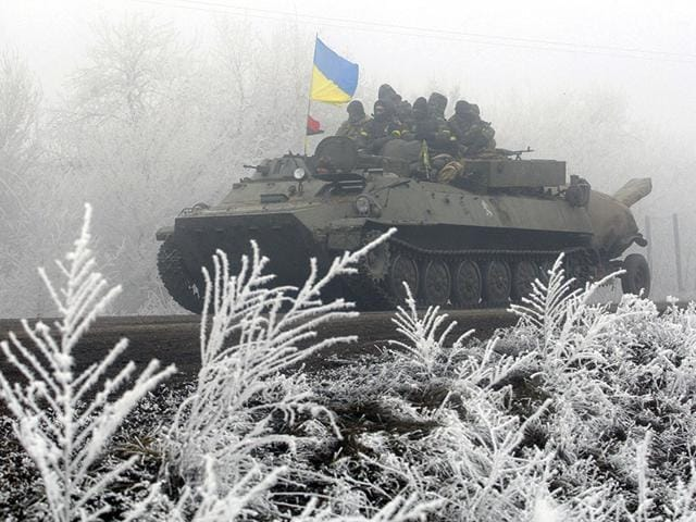 Ukrainian-servicemen-ride-on-a-tank-along-a-road-from-Artemivsk-to-Debaltseve-on-February-15-2015-AFP-photo