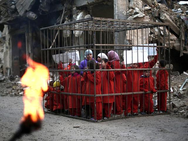 Syrian-children-wearing-orange-jumpsuits-stand-inside-a-cage-on-February-15-2015-placed-near-the-debris-of-a-building-destroyed-in-bombardment-by-Syrian-government-forces-on-the-rebel-held-Damascus-subrb-of-Douma-during-a-protest-to-denounce-the-continuing-killing-of-civilians-in-the-Syrian-conflict-and-the-failure-of-the-international-community-to-stop-the-carnage-During-the-protest-organised-by-Syrian-activists-the-children-were-immitating-Jordanian-air-force-pilot-Maaz-al-Kassasbeh-who-was-reportedly-burned-alive-by-jihadists-from-the-Islamic-State-IS-group-AFP-Photo-