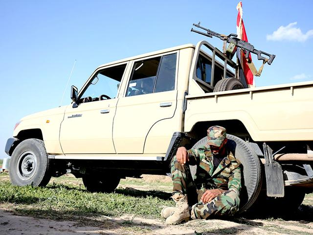 A-Shiite-militia-fighter-takes-a-rest-while-sitting-on-the-ground-against-a-pickup-truck-on-the-frontline-just-outside-Kirkuk-Iraq-AP-Photo