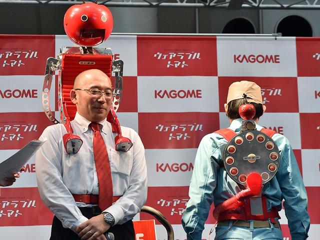 Japan-s-food-company-Kagome-employee-Shigenori-Suzuki-L-displyas-the-newly-developed-tomato-dispenser-for-marathon-runner-Tomachan-during-a-demonstration-ahead-of-this-weekend-s-Tokyo-marathon-in-Tokyo-Photo-AFP