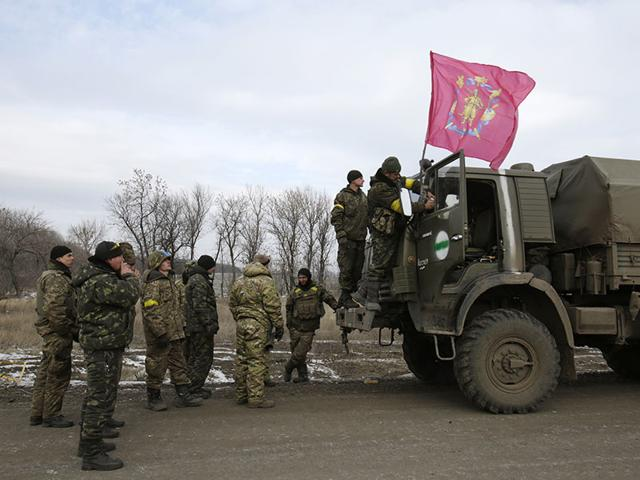 A-serviceman-fixes-a-flag-bearing-the-coat-of-arms-of-his-military-unit-on-a-truck-as-a-column-of-Ukrainian-forces-leave-Debaltseve-AFP-photo
