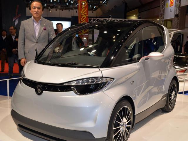 Japan-s-motorcycle-giant-Yamaha-Motor-president-Hiroyuki-Yanagi-displays-the-prototype-model-of-a-two-seater-commuter-Motiv-powered-by-electric-motor-or-gasoline-engine-at-the-press-preview-of-the-2013-Tokyo-Motor-Show-in-Tokyo-Photo-AFP