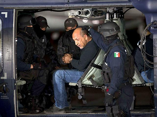 Federal-police-escort-who-they-identify-as-Servando-La-Tuta-Gomez--leader-of-the-Knights-Templar-cartel-as-he-sits-inside-helicopter-at-a-federal-hanger--in-Mexico-City-Reuters