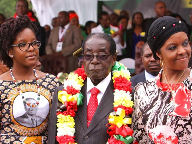 Zimbabwes-President-Robert-Mugabe-centre-is-flanked-by-his-daughter-Bona-left-and-wife-Grace-during-celebrations-to-mark-his-91st-birthday-in-the-resort-town-of-Victoria-Falls-Zimbabwe-AP-Photo
