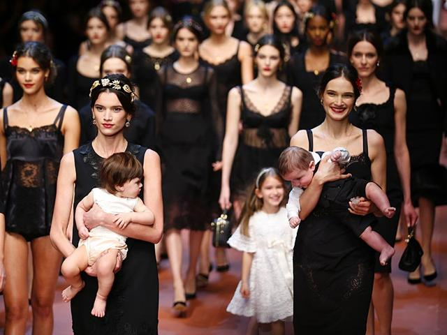 Eleven models walked with their own children while donning the collection's feminine, colorful, rose-covered silk dresses and skirts. (Reuters)
