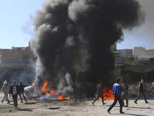 Civilians-and-civil-defense-members-run-past-flames-and-smoke-rising-at-a-site-hit-by-what-activists-said-was-a-barrel-bomb-dropped-by-forces-loyal-to-Syria-President-Bashar-al-Assad-in-the-Qadi-Askar-neighbourhood-of-Aleppo-Reuters