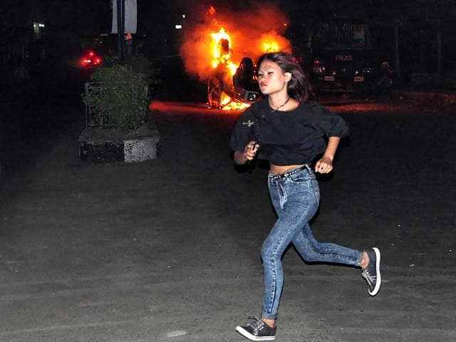 A-girl-runs-in-front-of-a-car-set-on-fire-by-a-mob-during-clashes-with-police-following-the-lynching-of-a-man-accused-of-rape-in-Dimapur-AP-Photo