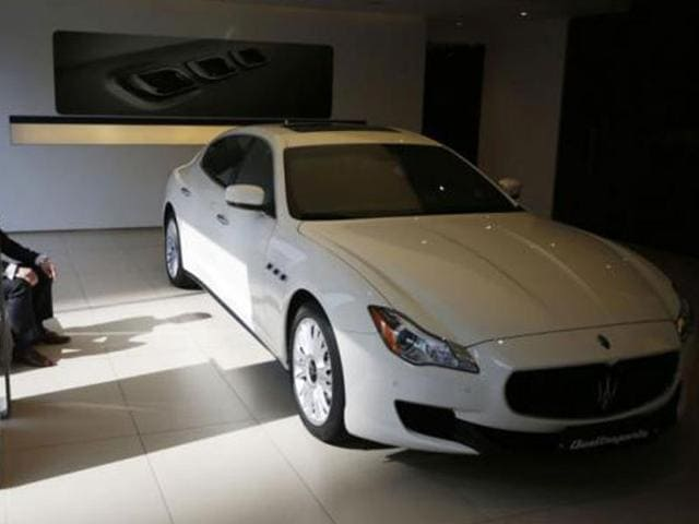 A-car-dealer-sits-in-front-of-a-Maserati-Quattroporte-car-at-its-dealership-in-Seoul-March-2-2015-Photo-Reuters