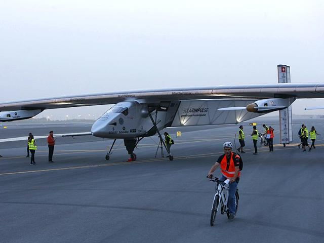 Members of the Solar Impulse 2 team stand next to the solar-powered plane before its take off from Muscat airport in Oman. (AFP File Photo)