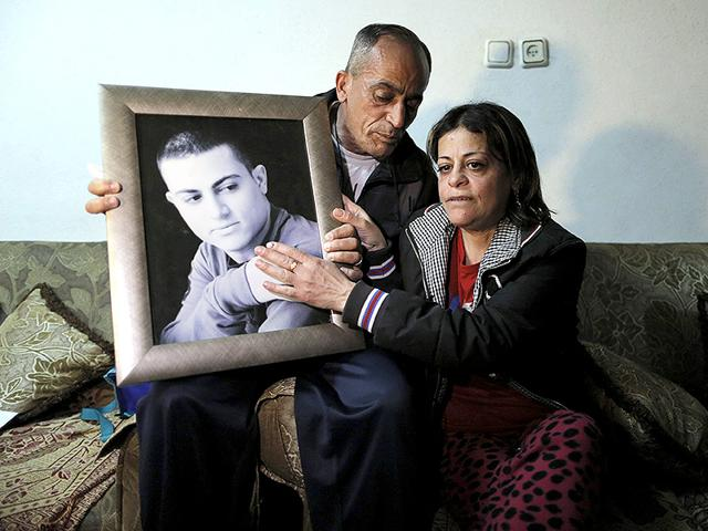 The-mother-and-father-of-Muhammad-Musallam-react-with-a-picture-of-him-in-their-East-Jerusalem-home-Reuters