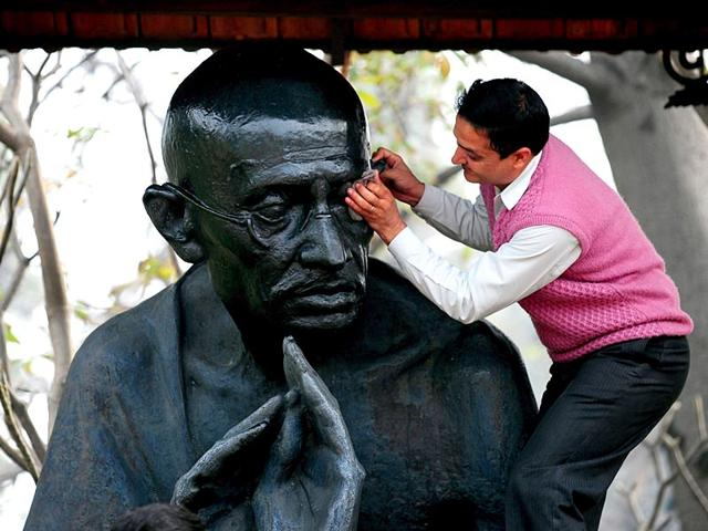 A-man-painting-the-statue-of-Mahatma-Gandhi-before-his-death-anniversary-at-The-Ridge-in-Shimla-on-Thursday-Santosh-Rawat-HT