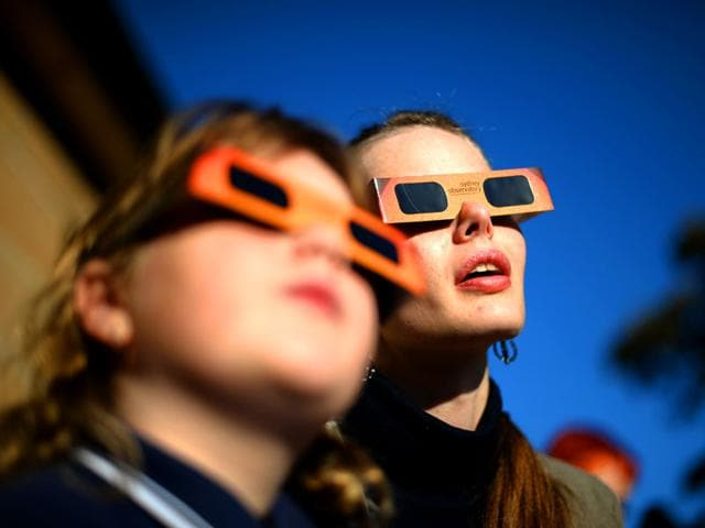 This-file-picture-dated-May-10-2013-shows-people-watching-a-partial-solar-eclipse-at-the-Sydney-Observatory-Die-hard-eclipse-junkies-from-around-the-world-are-expected-to-brave-polar-bears-and-frostbite-in-the-Arctic-on-March-20-2015-to-savour-three-minutes-of-total-darkness-when-the-moon-totally-blocks-the-sun-AFP-photo