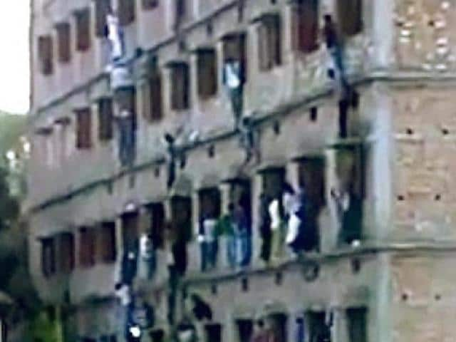 Family-members-and-friends-climb-walls-to-make-answer-chits-available-to-those-appearing-for-their-Class-10-exams-at-a-centre-in-Vaishali-Bihar-HT-Photo
