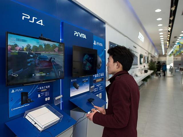 A-man-playing-with-a-Sony-PlayStation-4-in-a-shop-in-downtown-Shanghai-Photo-AFP