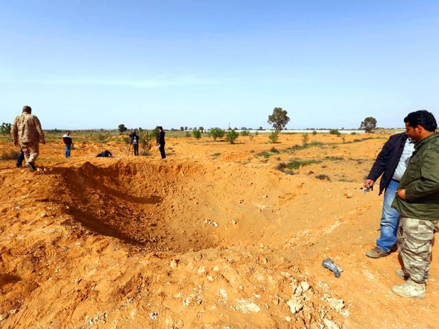 Members-of-the-Libya-Dawn-a-militia-alliance-stand-by-a-crater-on-the-ground-following-a-reported-air-raid-by-Libyan-pro-government-forces-in-Tarhuna-south-east-of-Tripoli-AFP-PHOTO