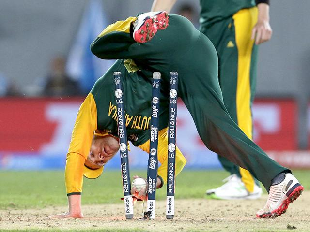 South-Africa-s-captain-AB-de-Villiers-tumbles-over-the-stumps-during-a-failed-run-out-attempt-on-New-Zealand-s-batsman-Corey-Anderson-during-their-Cricket-World-Cup-semi-final-match-in-Auckland-March-24-2015--REUTERS