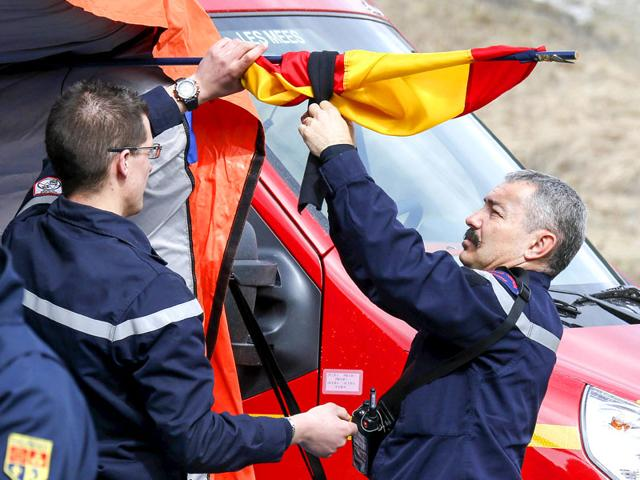 French-firefighters-install-a-black-ribbon-on-a-Spanish-flag-outside-a-tent-where-relatives-and-officials-are-due-to-pay-tribute-to-the-victims-of-the-Airbus-A320-crash-outside-Le-Vernet-near-Seyne-les-Alpes-Reuters