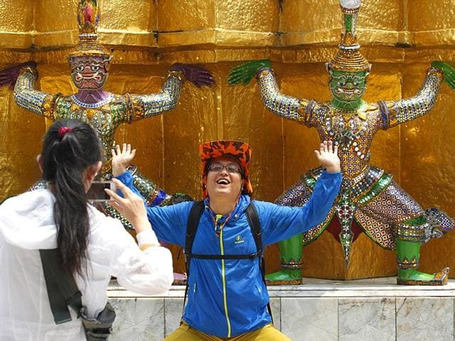 A-Chinese-tourist-strikes-a-similar-pose-to-statues-as-they-visit-the-Grand-Palace-in-Bangkok-Reuters
